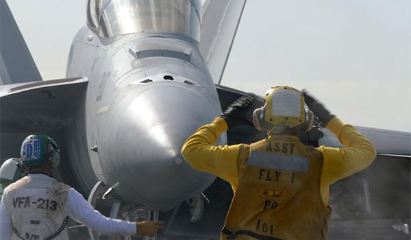A sailor assigned to the air department of George H.W. Bush guides an F/A-18F Super Hornet with VFA-213 to a catapult. (Photo: Petty Officer Third Class Nicholas Hall)