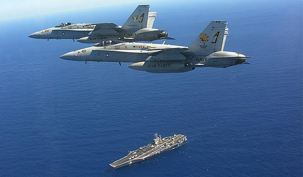 """George H.W. Bush's main offensive punch come from the four strike fighter squadrons of Carrier Air Wing Eight, accounting for 40 to 50 combat aircraft on board. Pictured, two F/A-18 Hornets with Strike Fighter Squadron VFA-87 (the """"Golden Warriors"""") above George H.W. Bush."""