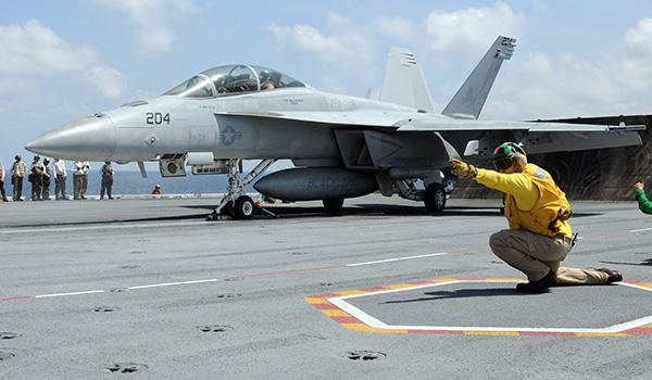 ON THE FLIGHT DECK: A shooter signals an F/A-18F Super Hornet with VFA-213 to launch on the flight deck of George H.W. Bush. (Photo: Daniel Moore)