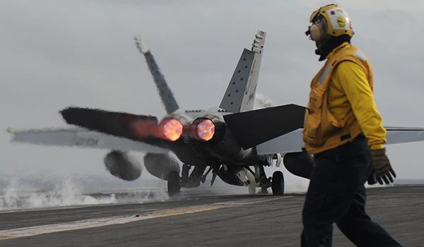 """An F/A-18F Super Hornet with Strike Fighter Squadron VFA-213 (the """"Black Lions"""") launches from the flight deck of George H.W. Bush. (Photo: Mass Communication Specialist Seaman Brian Stephens)"""