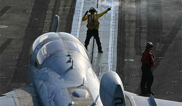 Sailors direct an EA-6B Prowler with VAQ-134 on the flight deck of George H.W. Bush. (Photo: Lieutenant Juan Guerra)