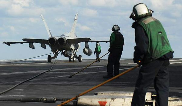 An F/A-18 Super Hornet comes to a stop on the arresting wire on the fligh deck of George H.W. Bush. (U.S. Navy photo by Mass Communication Specialist Seaman Brian Stephens/Released)