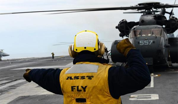 Aviation Boatswain's Mate (Handling) Second Class Steven Lily directs an MH-53E Sea Dragon on the flight deck of George H.W. Bush. (Photo: Mass Communication Specialist Third Class Kevin J. Steinberg)