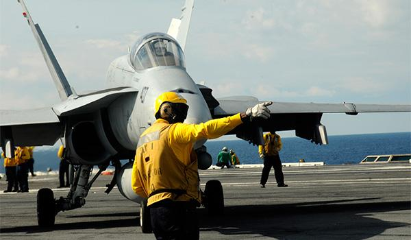 An air department sailor directs an F/A-18C Hornet assigned to VFA-15 on the flight deck of George H.W. Bush. (Photo: Petty Officer Third Class Brent Thacker)