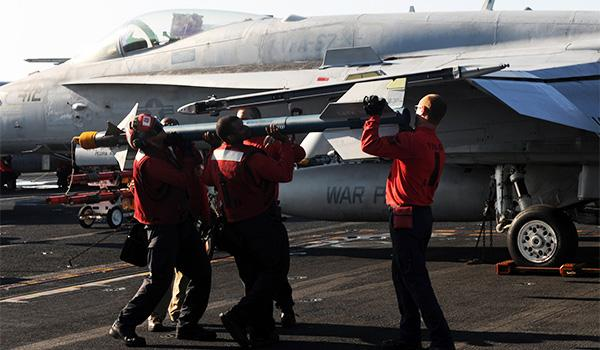 "Sailors assigned to VFA-87 (the ""Golden Warriors"") attach ordnance to an F/A-18A Hornet on the flight deck of George H.W. Bush. (Photo: Mass Communication Specialist Third Class Joshua Card)"
