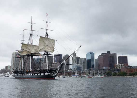 USS Constitution sets sail in Boston Harbor during the ship's first chief petty officer heritage week underway demonstration of 2014. More than 150 chief petty officer selects and mentors assisted Constitution's crew with setting the ship's three topsails during the underway to conclude a week of sail training aboard Old Ironsides. (U.S. Navy photo by Mass Communication Specialist 2nd Class John Benson/Released)