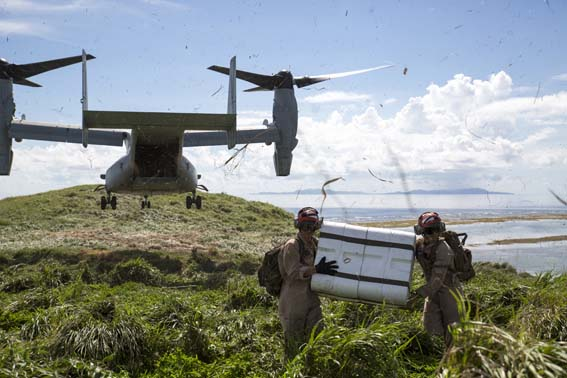 """Lance Cpl. Zachary Swisher, left, and Lance Cpl. Cornelio Vasquez, ordnancemen with Marine Aerial Refueler Squadron 152, carry a container of GTR-18 missiles, better known as """"Smokey SAMs,"""" away from an MV-22B Osprey during a threat reaction evolution on an island outside of Okinawa, Japan, Aug. 26, 2014. The threat reaction evolution is a chance for pilots to stay up to date on their qualifications while keeping an alert and aware mindset for any arising combat scenario."""