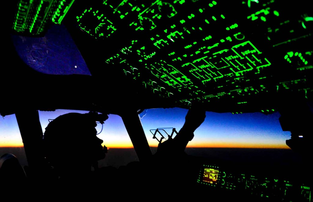 Capt. Erica Stooksbury 816th Expeditionary Airlift Squadron, C-17 Globemaster III pilot, adjusts the cockpit lighting controls as the sun rises after a humanitarian airdrop mission over Amirli, Iraq, Aug. 31, 2014. The two C-17s dropped 79 container delivery system bundles of fresh drinking water totaling 7,513 gallons. In addition, the two U.S. C-130s aircraft dropped 30 bundles totaling 3,032 gallons of fresh drinking water and 7,056 meals ready to eat. (U.S. Air Force photo by Staff Sgt. Vernon Young Jr.)
