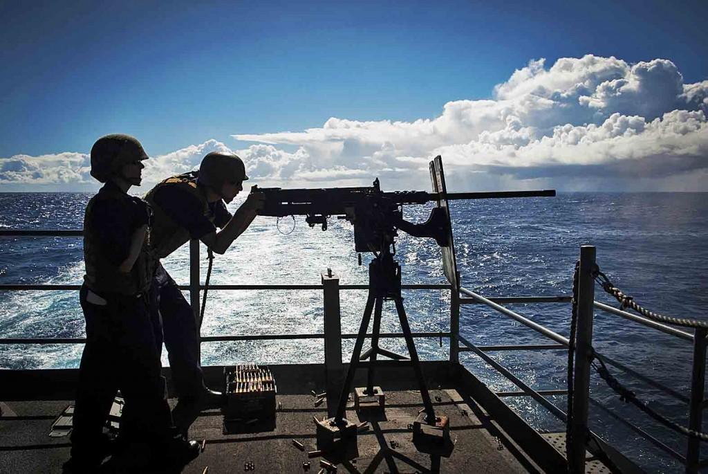 140829-N-HD510-084  PACIFIC OCEAN (Aug. 29, 2014) Gunner's Mate 2nd Class Ashley Jebens, from Devine, Texas, observes Aviation Ordnanceman Airman Joel Ochoa, from Riverside, Calif., fire an M2HB .50-caliber machine gun from the fantail of the aircraft carrier USS Carl Vinson (CVN 70). Carl Vinson is underway in the U.S. 3rd Fleet area of responsibility. (U.S. Navy photo by Mass Communication Specialist 2nd Class Scott Fenaroli/Released)