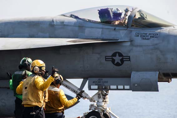 U.S. Sailors direct an F/A-18E Super Hornet aircraft assigned to Strike Fighter Squadron (VFA) 31 on the flight deck of the aircraft carrier USS George H.W. Bush (CVN 77) in the Persian Gulf Oct. 2, 2014, as the ship supports operations in Iraq and Syria. President Barack Obama authorized humanitarian aid deliveries to Iraq as well as targeted airstrikes to protect U.S. personnel from extremists known as the Islamic State in Iraq and the Levant. U.S. Central Command directed the operations. (U.S. Navy photo by Mass Communication Specialist 3rd Class Brian Stephens/Released)