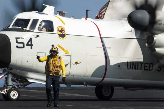 U.S. Navy Aviation Boatswain's Mate (Handling) 3rd Class David Vonhemert directs a C-2A Greyhound aircraft assigned to Carrier Fleet Logistics Support Squadron (VRC) 40 on the flight deck of the aircraft carrier USS George H.W. Bush (CVN 77) in the Persian Gulf Oct. 2, 2014, as the ship supports operations in Iraq and Syria. President Barack Obama authorized humanitarian aid deliveries to Iraq as well as targeted airstrikes to protect U.S. personnel from extremists known as the Islamic State in Iraq and the Levant. U.S. Central Command directed the operations. (U.S. Navy photo by Mass Communication Specialist 3rd Class Brian Stephens/Released)