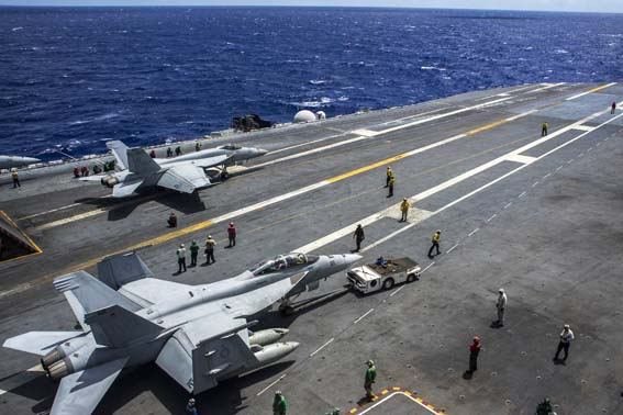 141001-N-GT589-002 WATERS NEAR GUAM (Oct. 1, 2014) Sailors handle F/A-18E Super Hornets on the flight deck of the U.S. Navy's forward-deployed aircraft carrier USS George Washington (CVN 73). George Washington and its embarked air wing, Carrier Air Wing (CVW) 5, provide a combat-ready force that protects and defends the collective maritime interests of the U.S. and its allies and partners in the Indo-Asia-Pacific region. (U.S. Navy photo by Mass Communication Specialist Seaman Everett Allen/Released)