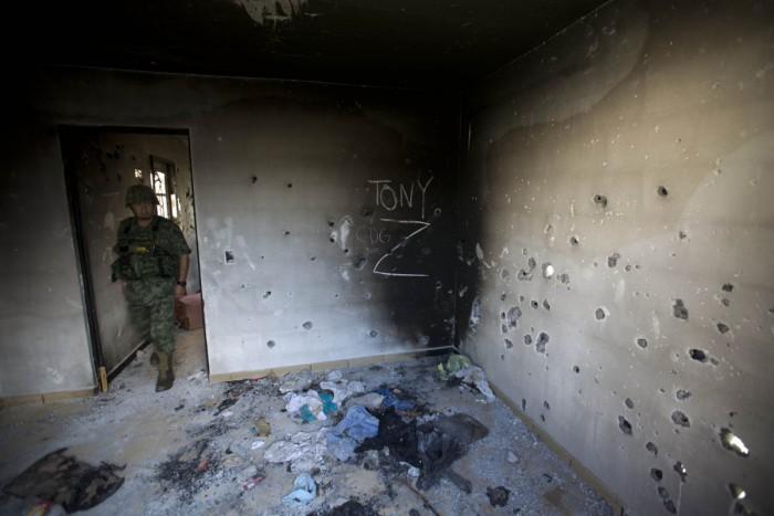 """Tentara Meksiko memasuki ruangan sebuah gedung milik Zetas yang diserbu. Tanda """"Z"""" adalah simbol kelompok ini"""