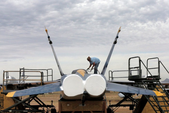 Petugas Jasa Katy Shank menyemprotkan cat penyegelan pada bekas NAVY Blue Angel F-18 di 309 Aerospace Maintenance and Regeneration Grup boneyard.