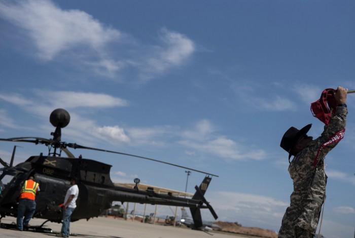 Seorang prajurit mengamankan melepas baling-baling helikopter Bell OH-58 Kiowa untuk disimpan di boneyard